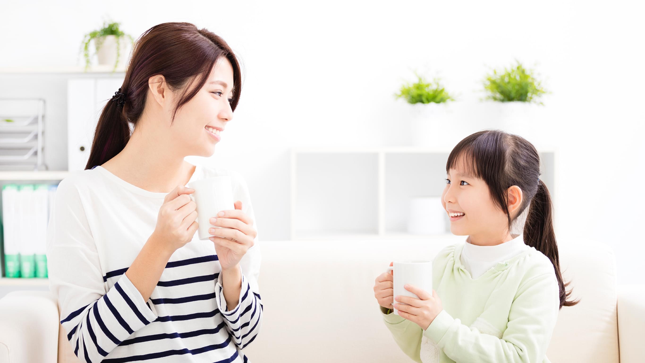 明るいリビングで温かい飲み物を飲む親子